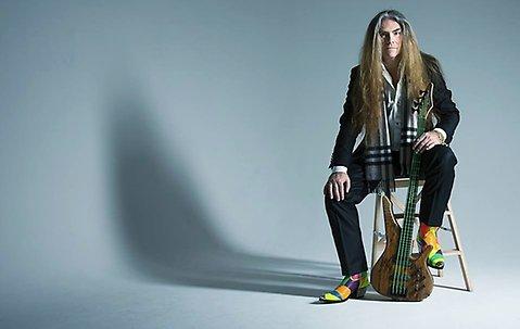 Foto på en man som sitter på en pall och håller i en elbas. mannen har långt hår. hans boots är färgglada.